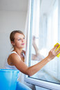 Pretty young woman doing house work washing windows shallow dof color toned image Stock Images