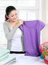 Pretty young woman doing the laundry at home Stock Photo
