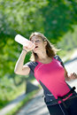 Pretty young woman doing skate is refreshed with water Stock Photography