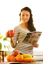 Pretty young woman drinking coffee reading news in front of the fruit basket Stock Photo