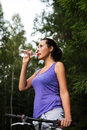 Pretty young woman drinks water outdoors summer Stock Images