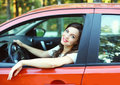 Pretty young woman driver behind wheel red car Royalty Free Stock Photo
