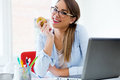 Pretty young woman eating an apple in her office. Royalty Free Stock Photo