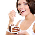 Pretty young woman eats a sweet cake isolated on white Stock Photography