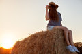 Pretty young woman in hat sitting on a hay bale Royalty Free Stock Photo