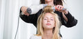 Pretty, young woman having her hair done by a hairstilist Royalty Free Stock Photo