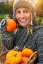 Pretty young woman holding basket of pumpkins Stock Photos
