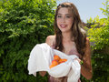 Pretty young woman holding fresh apricots auburn haired standing outdoors freshly picked organic in a towel in bright sunshine Royalty Free Stock Photo