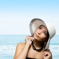 Pretty young woman holding hat on her head at the beach Royalty Free Stock Photos