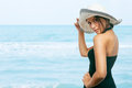 Pretty young woman holding hat on her head at the beach Stock Image