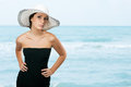 Pretty young woman holding hat on her head at the beach Royalty Free Stock Image