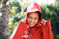 Pretty young woman holding a raincoat hat on head Royalty Free Stock Photos