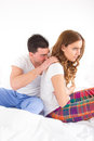 Pretty young woman ignoring her man partner in her bed during a women men conflict Royalty Free Stock Photography