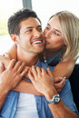 Pretty young woman kissing her boyfriend Royalty Free Stock Photo