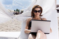 Pretty young woman with laptop on the beach Stock Photography
