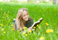 Pretty young woman lying on grass with dandelions reading a book Royalty Free Stock Photo