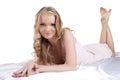 Pretty young woman lying on white sheet Stock Photo