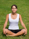 Pretty young woman meditating on grass Stock Image