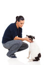 Pretty young woman playing her pet dog white background Royalty Free Stock Photo