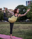 Pretty Young Woman Practicing Yoga in the Park (Dancer Pose) Royalty Free Stock Photo