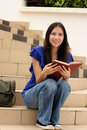Pretty young woman reading a book at staircase Stock Photo