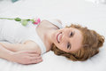 Pretty young woman resting in bed with a rose