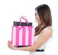 Pretty young woman with shopping bags after clearance sale surprised looking at the bag on a white background Royalty Free Stock Photography