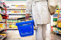 Pretty, young woman with a shopping basket buying groceries Royalty Free Stock Photo