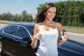 Pretty young woman is showing okay sign cheerful girl giving thumbs up and smiling she standing near her new car and holding the a Royalty Free Stock Photography