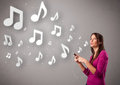 Pretty young woman singing and listening to music with musical n Royalty Free Stock Photography