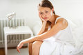 Pretty, young woman sitting on bed Royalty Free Stock Photo