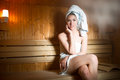 Pretty young woman sitting relaxed in a wooden sauna.Young woman in white towel sitting in Finnish sauna. Royalty Free Stock Photo