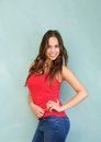 Pretty young woman smiling in red shirt and blue jeans portrait of a Stock Photos
