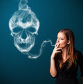 Pretty young woman smoking dangerous cigarette toxic skull smoke Royalty Free Stock Image