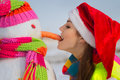 Pretty young woman with a snowman Royalty Free Stock Images