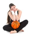 Pretty young woman in sports wear sitting on floor with a basketball