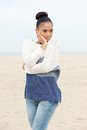 Pretty young woman standing on beach alone in sweater and jeans portrait of a Royalty Free Stock Image