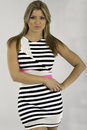 Pretty young woman is a striped casual dress looking at camera shot on grey background Stock Photography