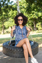 Pretty young woman in tire swing Royalty Free Stock Photo