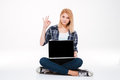 Pretty young woman using laptop while make okay gesture. Royalty Free Stock Photo