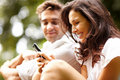 Pretty young woman using mobile with her boyfriend Royalty Free Stock Photo