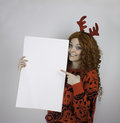 Pretty young woman wearing antlers and holding blank sign beautiful red sweater red Stock Image