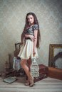 Pretty young woman with white bird s cage and long hair in rustic interior Royalty Free Stock Photo