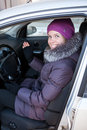 Pretty young woman in winter clothes sitting in car Stock Image