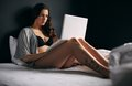Pretty young woman working on a laptop in bedroom portrait of wearing lingerie while sitting bed attractive female model using Stock Photo
