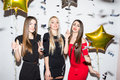 Pretty young women with star shaped balloons and confetti dancing and having party Royalty Free Stock Photo