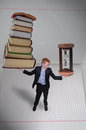 Price of knowledge schoolboy holding pile books in one hand and sundial in other Stock Image