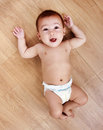 Priceless expressions of cute little baby lying on the floor Royalty Free Stock Photo