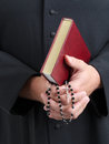 Priest with bible and rosary closeup of catholic s hands holding the holy Royalty Free Stock Images