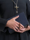 Priest with bible and rosary closeup of catholic s hands holding the holy Stock Image
